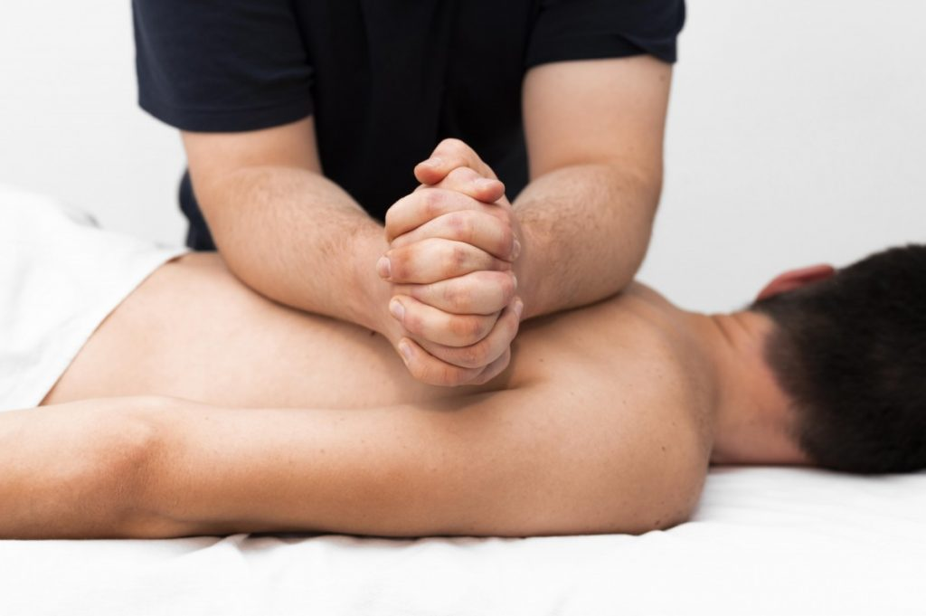 Knots in Knead front-view-physiotherapist-massaging-man-s-back-1024x681